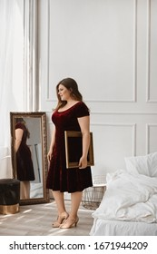 Young plus size model girl in red velvet dress posing in the studio. Young plump woman with nude makeup in modish dress posing in the interior. Concept of XXXL fashion. Concept of beauty and luxury