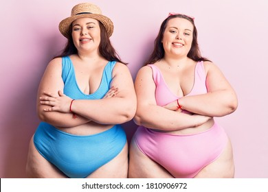 Young plus size twins wearing bikini happy face smiling with crossed arms looking at the camera. positive person.