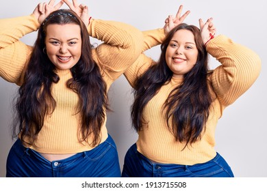 Young plus size twins wearing casual clothes posing funny and crazy with fingers on head as bunny ears, smiling cheerful