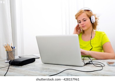 A young plus size woman listening to Audio in front of a laptop computer.