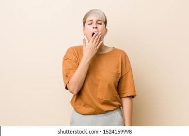 Young plus size woman with short hair yawning showing a tired gesture covering mouth with hand.