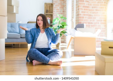Young plus size woman sitting on the floor around cardboard boxes moving to a new home clueless and confused expression with arms and hands raised. Doubt concept.