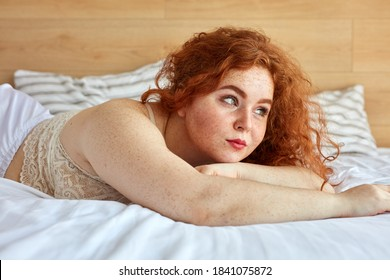 young plus-size redhead woman on the bed in the bedroom in the morning,attractive female has beautiful breasts. fat woman in white underwear on large bed with white linens