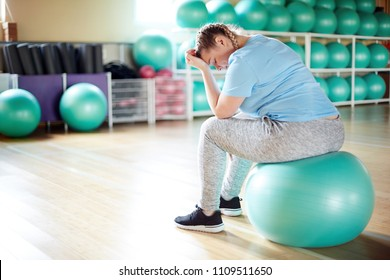 Young plus-sized woman sitting on fitball in gym and thinking about her bad fitness results