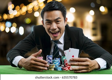 The young poker gambler is showing a pair of red aces and smiling with glad to win the poker cards and holding bets a large stack, on casino background