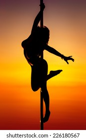 Young pole dance woman silhouette on sunset background.