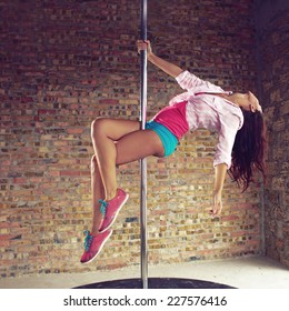 Young pole dancer woman wearing colorful sports wear and sneakers trains on grunge interior with brick walls, square composition