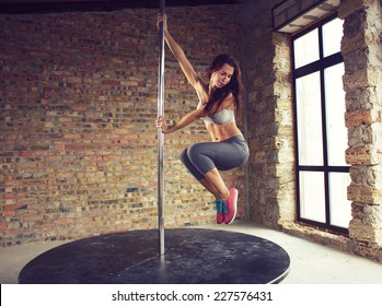 Young pole dancer woman wearing grey sports wear and colorful sneakers trains on grunge interior with brick walls