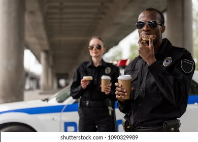 young police officers having coffee break with doughnuts in front of police car
