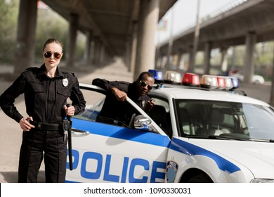 young police officers standing near car under bridge