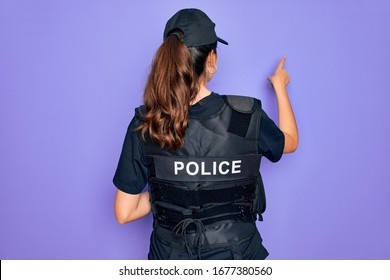 Young police woman wearing security bulletproof vest uniform over purple background Posing backwards pointing ahead with finger hand