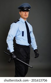 Young policeman in uniform holds nightstick on gray background
