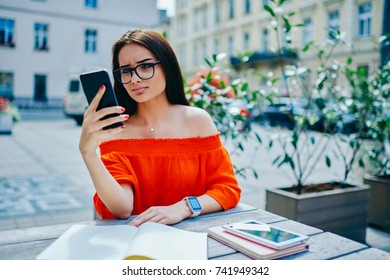 Young pondering female in spectacles watching interesting video in webpage on smartphone connected to wireless internet outdoors.Charming hipster girl checking email during free time at street