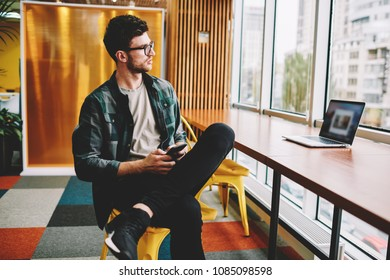 Young pondering skilled male employee dressed in trendy clothing planning working schedule while sitting in modern office.Pensive smart hipster guy in eyeglasses thinking about ideas for startup