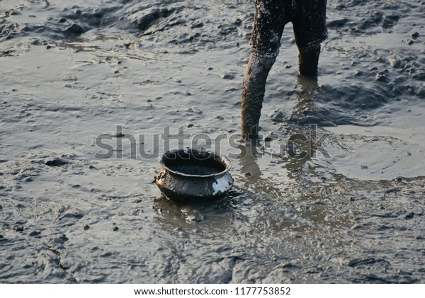 Young poor boy fishing around a muddy pond isolated unique photo