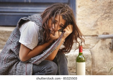 young poor girl drunk sitting in city street