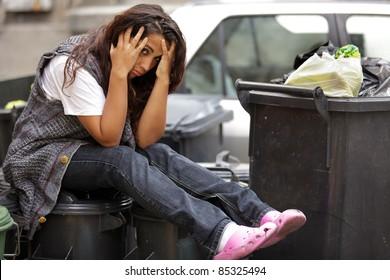 young poor girl very sad sitting on bin trash