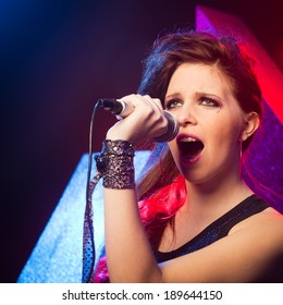 Young pop star girl singing on stage close up.
