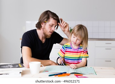 Young positive bearded man helping his daughter in preschool age to color paper on kitchen