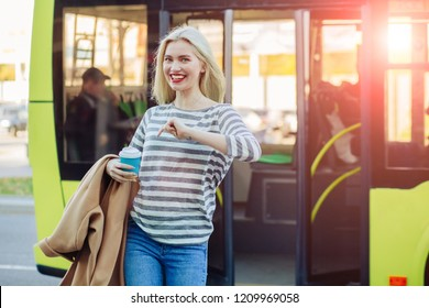 Young positive blond hipster woman passenger with coffee cup getting off the yellow bus in vacation. Lifestyle and everyday routine concept.