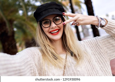 Young positive blonde woman wearing stylish trendy cap and cozy white sweater, making selfie in the street, smiling and looking on camera, making v science by her hands, jewelry and accessories.