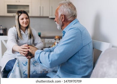 Young positive caregiver taking care of senior man in nursing home