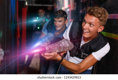 Young positive cheerful glad smiling guy holding colored laser guns and took aim during laser tag game in labyrinth