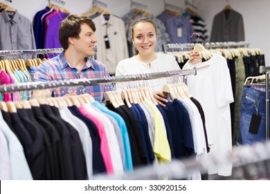 Young positive couple choosing clothes at store. Focus on woman