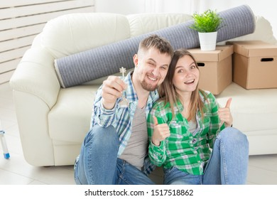 Young positive couple holding keys to a new apartment while standing in their living room. Housewarming and family mortgage concept.