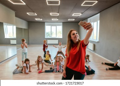 Young and positive dance teacher making a selfie with children while having choreography class. Dance school. Teacher and kids