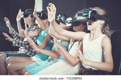 Young  positive daughter is impressed of VR with family in the room.