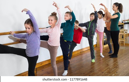 Young positive  efficient ballet dancers exercising in ballroom