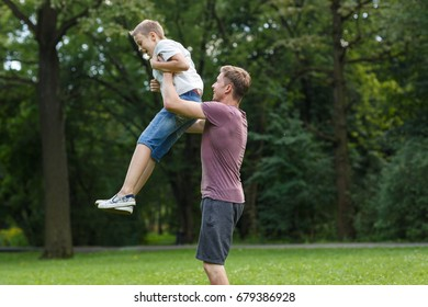 A young positive father raised his son in the park in the park against the background of green trees. Father and son having fun in the park