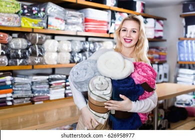 Young  positive female customer boasting purchased home textiles in textile shop