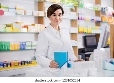 Young positive female pharmacist offering help in choosing at counter in pharmacy