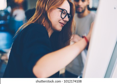Young positive female worker carefully writing down general concepts of business startup project to board standing in coworking space. Beautiful woman employer in eyeglasses brainstorming on flipboard