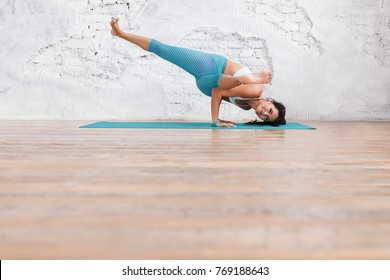 Young positive female yoga instructor doing difficult exercise with raising the legs on rug on the wooden floor in the gym