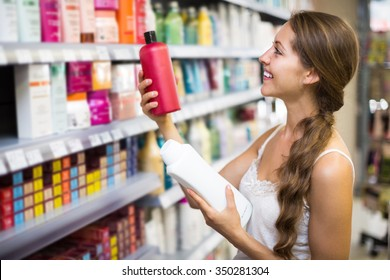 Young positive girl buying shampoo in shopping mall