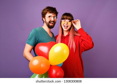 Young positive hipster couple of pretty young woman with unusual pink hairs and handsome man with bread having fun together, trendy casual clothes, holding party air balloons, purple background.