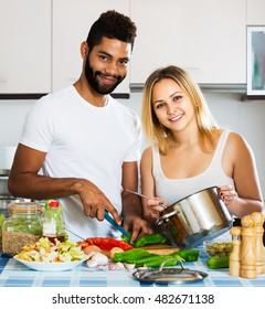 Young positive interracial couple cooking vegetables and laughing in home interior