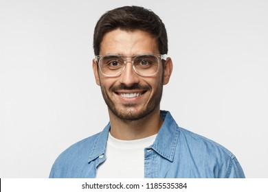 Young positive man with eyeglasses, dressed in light blue shirt and white t-shirt, looking at camera with happy smile, isolated on gray background
