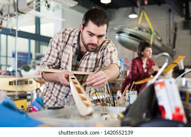 Young positive man hobbyist engaged in creating plane models in aircraft workshop