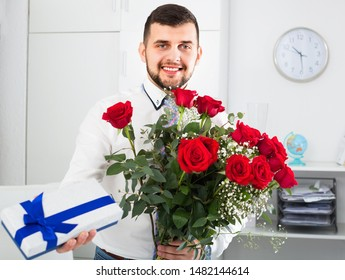 Young  positive man ready to present flowers and gift at holiday in office