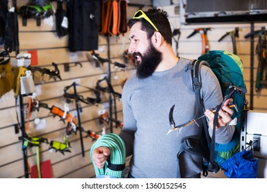 Young positive man selecting climbing equipment in sports equipment shop