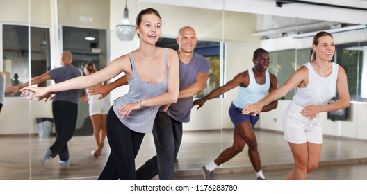 Young positive people dancing lindy hop during group training in dance hall