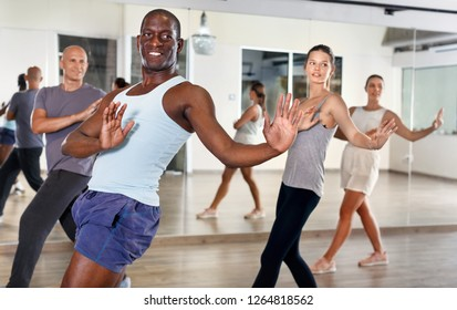 Young positive people dancing a lindy hop during group training at a dance hall