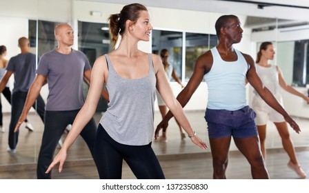 Young positive people dancing lindy hop during a group training at a dance hall
