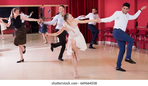 Young positive people dancing lindy hop in pairs in dance hall