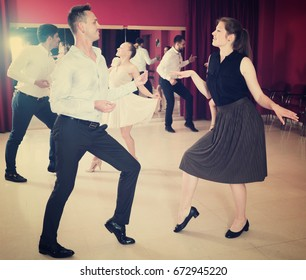 Young positive people dancing twist in pairs