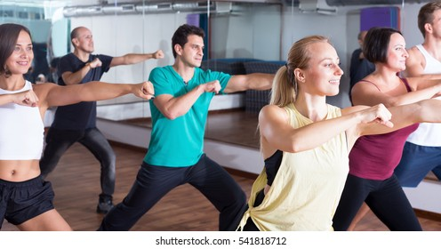 Young positive  people dancing  zumba elements in dancing hall indoor